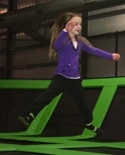 Girl Jumping on Trampoline at Indoor Park
